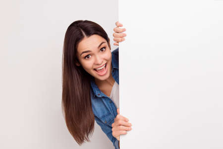 Happy amazed young girl is popping out from white blank banner