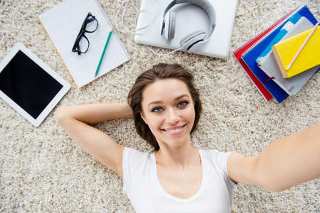 earbud: Top view selfie of a young successful beautiful lady lying on the carpet and smiling