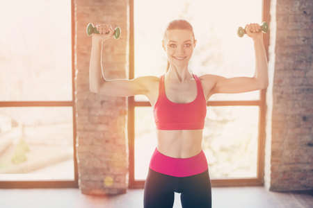 Pretty brunette working out with dumbbells in sunny room. She is excited and glad of the rwsults of her trainings Stock Photo