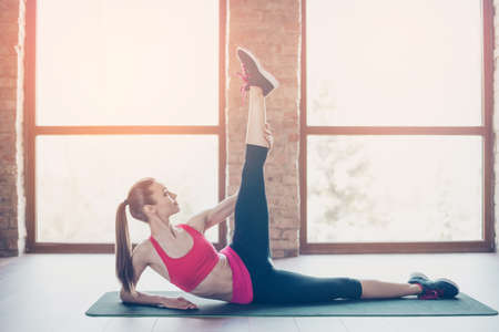 Young slim fit woman is doing stretching before start her training, to be bendy and flexible, not to hurt her muscles