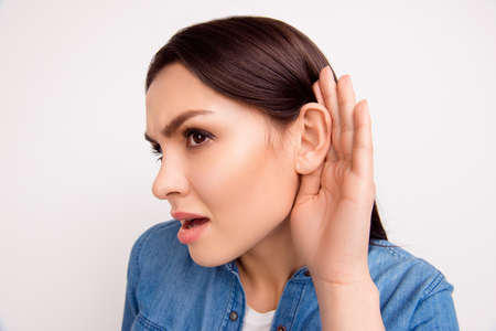 Close up portrait of brunette girl with cupped hand curiously listening to gossip or secret Stock Photo
