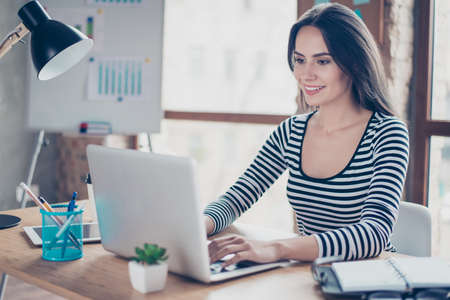 Smiling happy young lady sitting at the table in office and typing on laptop