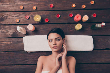 Cute nice relaxed young woman laying in spa salon on towel Stock fotó