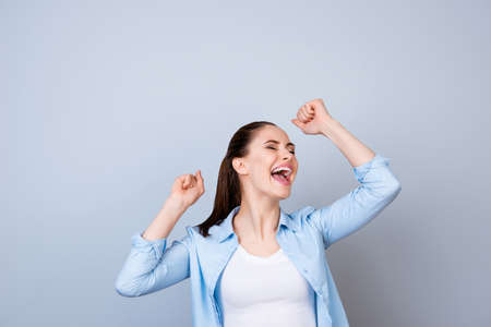Portrait of happy excited woman screaming and triumphing with raised hands