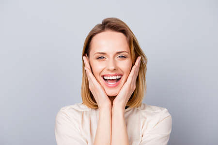 Close up portrait of funny cute young woman laughing and touching her cheeks