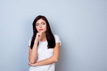 Portret van jonge gedachte vrouw in witte t-shirt aanraken haar kin geïsoleerd op grijze achtergrond Stockfoto