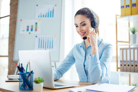 Portrait of young smiling happy woman in headphones working as operator of call center