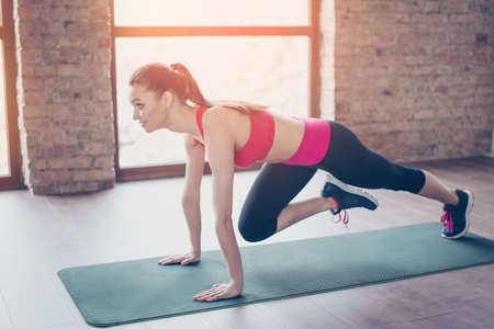 Pretty young slim girl stretching her legs by doing exercise. She is training on the green mat on the floor in sunny room, girl is happy and smiles