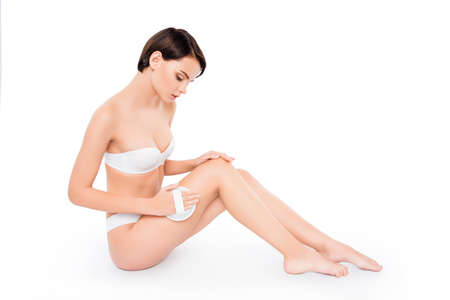 bodycare: Young cute girl sitting on the floor peeling legs Stock Photo
