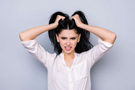 Bad mood. Overworked furious stressed young  woman in rage holding head with black hair