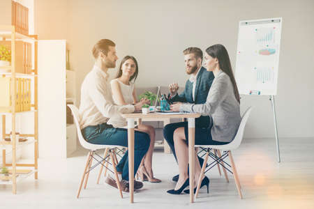 formalwear에서 심각 하 게 논의하는 동안 현대적인 직장에서 테이블에 앉아 젊은 비즈니스 사람들 스톡 콘텐츠