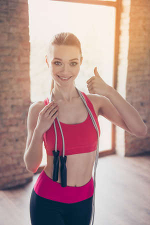bodycare: Great job! Happy young sportwoman in stylish training outfit with jumping rope on her shoulders is smiling and showing thumb up