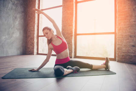 Young sportwoman is making stretching on green mat on the floor of sunny room. She is focused and serious, concentrated on procces