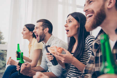 they are watching: Close up of four friends, fans of games, sitting at the sofa in nice cozy home, watching the game and showing excitement, amazement, shock. They are eating, drinking and shouting