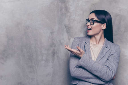 Portrait of excited  pretty business woman in glasses and jacket stands on a gray background, stares surprised and points with her hand Stock Photo