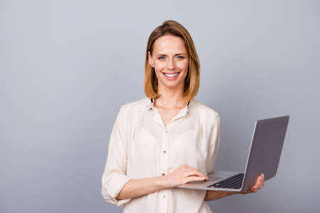 Portrait of charming woman in shirt using computer for her work standing against gray background Фото со стока
