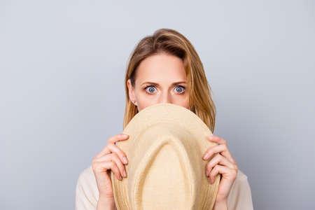 Sluit omhoog portret van leuke jonge vrouw die stilte houden en haar gezicht achter hoed verbergen