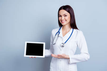 Portrait of smiling young doctor in white coat showing the screen of digital tablet in her hand