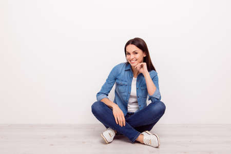 Nice-looking young cheerful girl touching her chin and sitting on the floor with crossed legs against white background