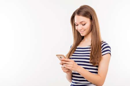 ストライプの t シャツがスマート フォンを保持し、sms を送信する白い背景で隔離のかなり若い女性
