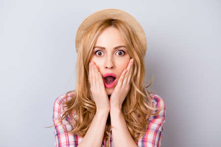 Close up portrait of pretty surprised woman with opened mouth in hat and checkered shirt isolated on gray background Stock fotó