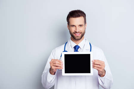 Smart young smiling  doctor in white coat demonstrating the screen of his digital tablet on gray background Stock Photo