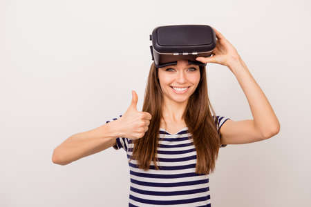 Excited young smiling girl showing thumb up after using goggles of virtual reality