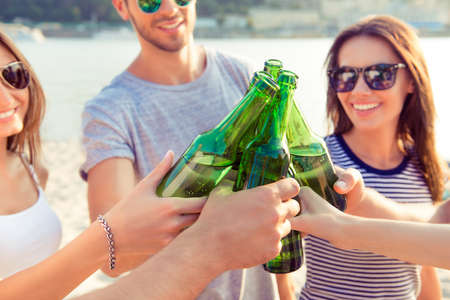 Concept of celebration and friendship. Group of happy smiling young people in sunglasses clinking bottles Stock Photo