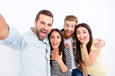 Un groupe d'amis excités qui font de l'auto-amour sur la caméra du smartphone montrant de grandes émotions d'étonnement et d'excitation sur fond blanc en vêtements décontractés