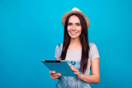 Mooie lachende vrouw in jeans overall en zomer hoed met digitale tablet en proberen goede plek voor haar vakantie te vinden Stockfoto