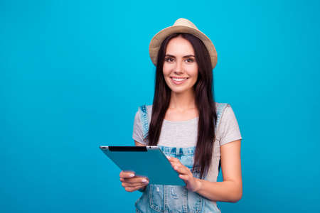 beforehand: Pretty smiling woman in jeans overalls and summer hat holding digital tablet and trying to find good place for her holidays Stock Photo