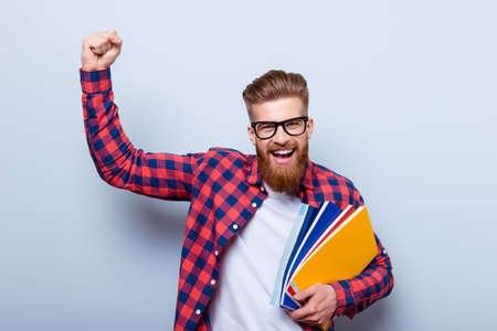 Young cheerful student in glasses and in checkered shirt with books in hands celebrating ending of exams
