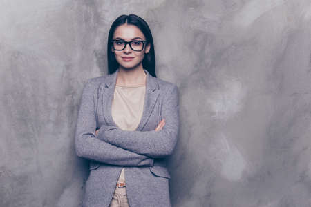 assured: Young smart beautiful businesswoman in glasses stands on gray background with  folded her hands and looks directly to the camera Stock Photo