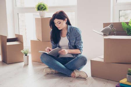 Trautes Heim, Glück allein! Junges Mädchen in der zufälligen Kleidung, die mit den gekreuzten Beinen auf dem Boden ihrer neuen Wohnung sitzt. Sie ist gerade eingezogen und hat über ihre Gefühle im Tagebuch geschrieben. Viele ausgepackte Kartons in ihrer Nähe Standard-Bild
