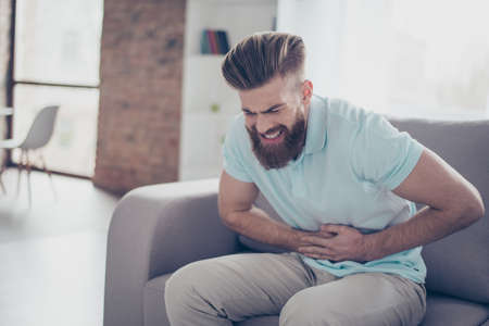 constipation symptom: Sad young bearded man is suffering from stomach pain, ache is very hard. He is alone at home, sitting on couch