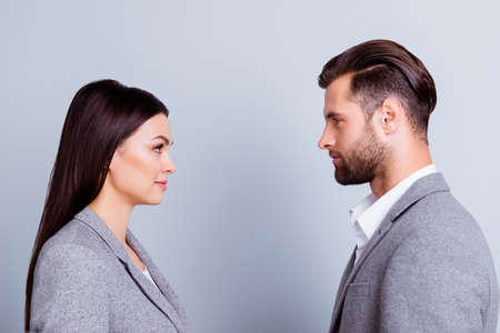 Concept of confrontation in business. Close up photo of two young serious confident people standing face-to-face to each other