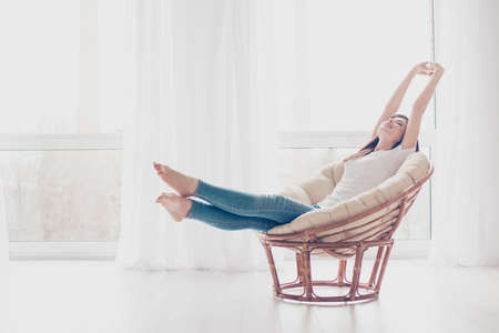 Young girl is stretching in modern armchair in light livingroom. She is sleepy and dreamy, wearing casual clothes