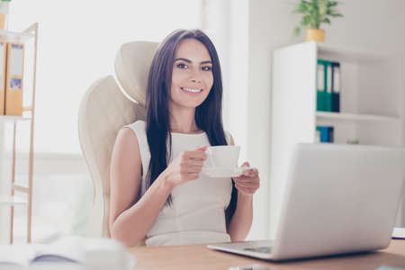 Young attractive business lady is having a cup of coffee at her workplace. She is happy and thinking of the vacation which is coming Reklamní fotografie