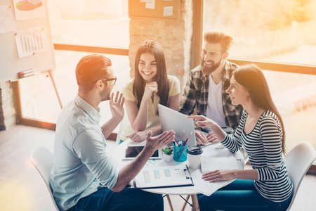 Cheerful partners are discussing an idea of new start-up by smiling and enjoying each others company in a light modern workplace
