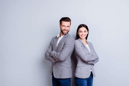 Concept van partnerschap in het bedrijfsleven. Jonge man en vrouw die zich rijtjes met gekruiste handen tegen grijze achtergrond bevinden