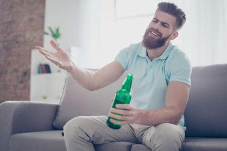 Vergüenza joven se siente frustrado por la pérdida del equipo en el juego que está viendo. Guy está tomando cerveza y sentado en el sofá en la sala de estar