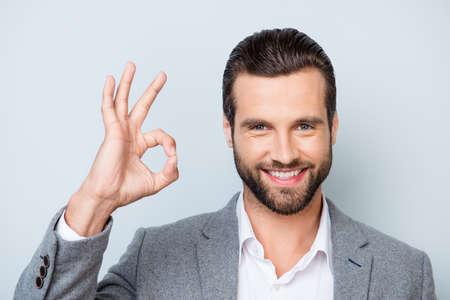 スタイリッシュな髪型と灰色の背景に ok サインを示す正装で幸せな男の写真をクローズ アップ