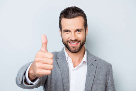 Young smiling handsome worker in formal clothing demonstrating thumb up against gray background Zdjęcie Seryjne