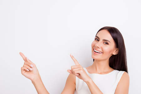 Successful smiling businesslady is pointing up with fingers. She is in isolated on the snow white background Banque d'images