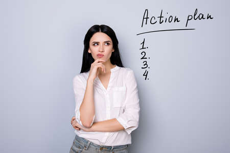 Portrait of cute young  woman with pouted sensual lips and black hair fink about new idea and looking at drawn list of action plan. Copy space on item