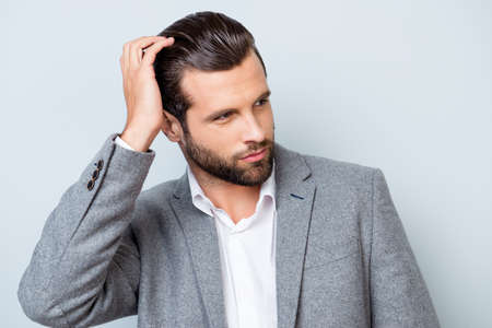 Close up portrait of handsome confident masculine man in jacket touching his hair