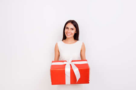 Happy smiling cute woman holding big red present box on white background. She is smiling, dressed in white smart dress