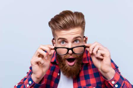 Close up portrait of shocked amazed man in checkered shirt touching his glasses