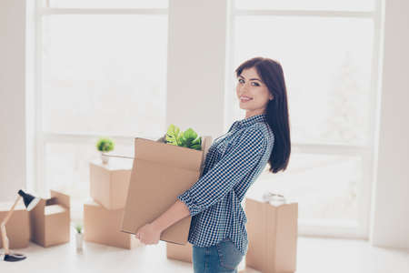 Young cheerful successful woman moving to new nice place and holding box with her belongings. The room is very light and bright, a lot of boxes with stuff around her