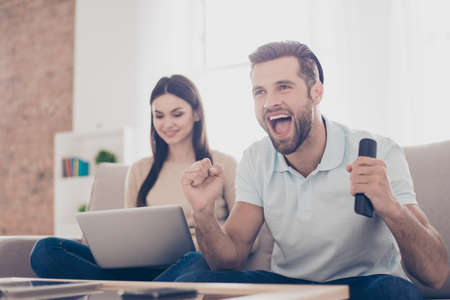 Verheiratete junge Leute verbringen ihr Wochenende zu Hause zusammen. Er schaut sich das Spiel an und sie sucht nach Informationen in ihrem Laptop Standard-Bild - 80778599